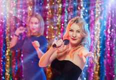 Girls Having fun at karaoke. Portrait of young pretty blonde women singing at karaoke with her girlfriends Royalty Free Stock Image
