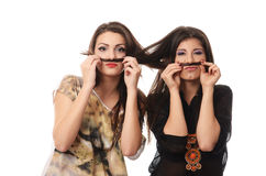 Girls having fun and making mustaches out of each others hair Stock Photography