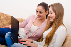 Girls having fun with notebook Stock Images