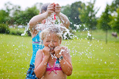 Girls having fun outdoor with water balloons Royalty Free Stock Photos