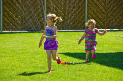 Girls having fun with sprinkler in garden Royalty Free Stock Images