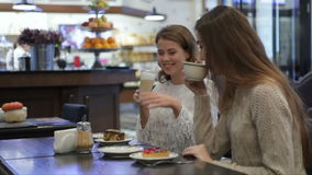 Girls having fun talking in coffee shop. Two girls having fun talking in coffee shop. The girls or womans begin their morning with fresh pastries and coffee in a stock video footage