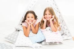 Girls having fun tipi house. Girlish leisure. Sisters share gossips having fun at home. Pajamas party for kids. Cozy. Place tipi house. Sisters or best friends royalty free stock images