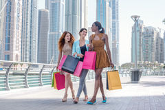 Girls having fun together shopping. Beautiful girl in dress hold Stock Photos