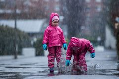Girls are having fun in water on street in cold autumn day, girls splashing water in rain, cheerful girls enjoying cold weather. Girls are having fun in water on stock photos
