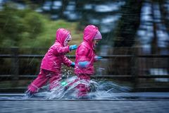 Girls are having fun in water on street in cold autumn day, girls splashing water in rain, cheerful girls enjoying cold weather. Girls are having fun in water on royalty free stock photo