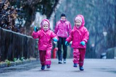 Girls are having fun in water on street in cold autumn day, girls splashing water in rain. Happy and cheerful girls enjoying cold weather, kids in pink rain royalty free stock photography