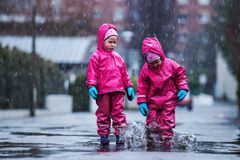 Girls are having fun in water on street in cold autumn day, girls splashing water in rain, cheerful girls enjoying cold weather. Girls are having fun in water on stock photography