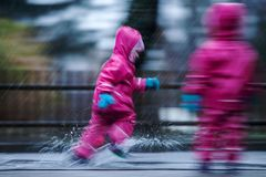 Girls are having fun in water on street in cold autumn day, girls splashing water in rain, cheerful girls enjoying cold weather. Girls are having fun in water on stock image