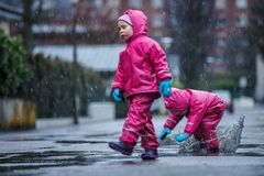Girls are having fun in water on street in cold autumn day, girls splashing water in rain, cheerful girls enjoying cold weather. Girls are having fun in water on royalty free stock photography
