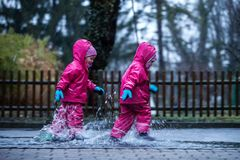 Girls are having fun in water on street in cold autumn day, girls splashing water in rain, cheerful girls enjoying cold weather. Girls are having fun in water on royalty free stock image