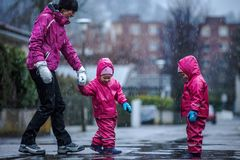 Girls are having fun in water on street in cold autumn day, girls splashing water in rain. Happy and cheerful girls enjoying cold weather, kids in pink rain stock images