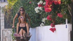 Girls having fun in a wheelbarrow with flowers stock footage