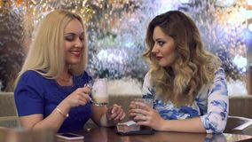 Girls are having a great time in the company of each other in a cafe. Two attractive girls have fun chatting in cafe stock video