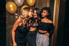 Girls having a great time at nightclub. Shot of three girls in the nightclub having a great time. Group of female friends standing together in party at pub Royalty Free Stock Photo