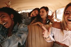 Girls having great time on road trip. Young female friends on a road trip traveling by a car and having a great time. Group of women enjoying car ride stock photo