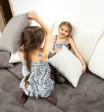Girls having pillow fight on bed Stock Image