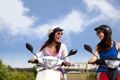 Girls having road trip on scooter. Happy girls having road trip on a scooter Royalty Free Stock Photo