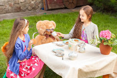 Girls having tea party with teddy bear at yard Royalty Free Stock Photos