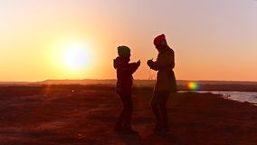 Girls with headphones dancing to music, young girls with phone listening to music on headphones against the sunset. stock video footage