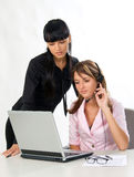 Girls with headset and laptop. Attractive girls with headset and laptop working together Royalty Free Stock Photo