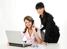 Girls with headset and laptop. Attractive young girls with headset and laptop on white background stock images