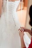 Girls help to the bride to button wedding dress Royalty Free Stock Images