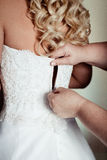 Girls help to the bride to button wedding dress Stock Photos