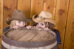 Girls hiding behind barrel Royalty Free Stock Image