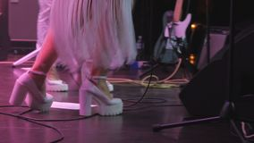 Girls on high heels dancing at the stage on the concert. The musician on the concert. View on the legs of singer at the stage. Performers of music dancing at the stock video footage