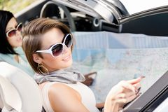 Girls with the highway map in the car Stock Photos