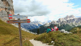 Girls hikers resting near of Cinque Torri towers mountains at the Dolomites. Italy n stock footage