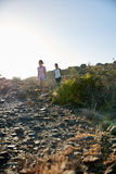 Girls hiking down rocky mountain side Stock Photo
