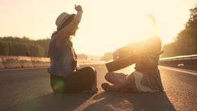 Girls hippie sing songs and you play the guitar. two hipsters sitting on the roadway at sunset stock video