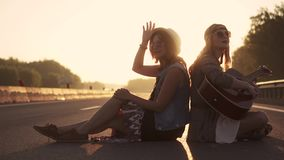 Girls hippie sing songs and you play the guitar. two hipsters sitting on the roadway at sunset stock video footage
