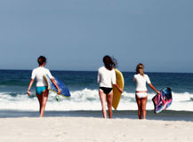 Girls hit the surf. Girls going boogie board riding Stock Photography