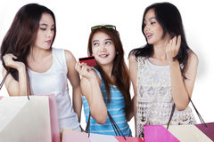 Girls hold credit card and shopping bags in studio Royalty Free Stock Images
