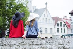 Girls hold hands sitting on the fence Royalty Free Stock Photo