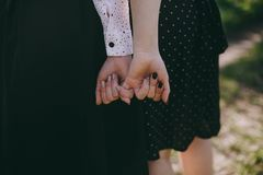 Girls hold their little ones one by one in black skirts in a spring park royalty free stock image