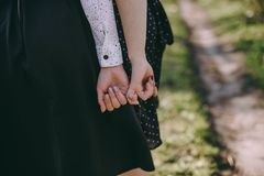 Girls hold their little ones one by one in black skirts in a spring park royalty free stock images