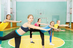 Girls holding balance standing on one leg in gym Stock Image