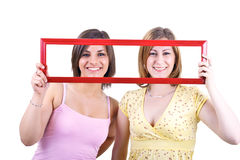 Girls holding frame Royalty Free Stock Photography