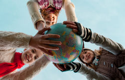 Girls holding a globe. Three girls holding a globe Royalty Free Stock Images