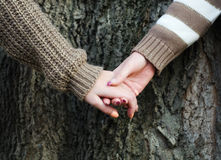 Girls holding hands against tree bark Stock Photography