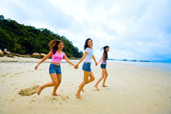 Girls holding hands at the beach Stock Photo