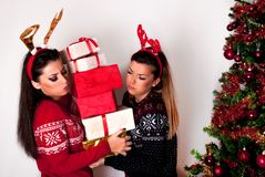 Girls holding many heavy gift boxes next to Christmas tree in sweater and reindeer horns royalty free stock image