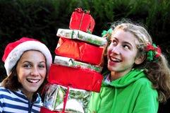 Girls holding pile of xmas presents. Portrait of two girls holding xmas presents Royalty Free Stock Photos