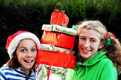 Girls holding pile of xmas presents. Portrait of two girls holding xmas presents Royalty Free Stock Photography