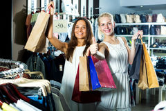 Girls holding shopping paper bags. Two beautiful girls holding shopping paper bags among racks with clothes in shop stock photo