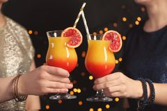 Girls holding tequila sunrise cocktails. In night club Stock Photography